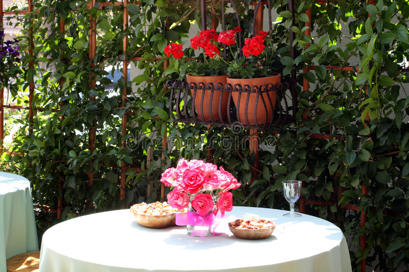 Outdoor Dining with Flowers. An outdoor table with a tablecloth and pink flowers on a vase. Potted red flowers near the table royalty free stock images