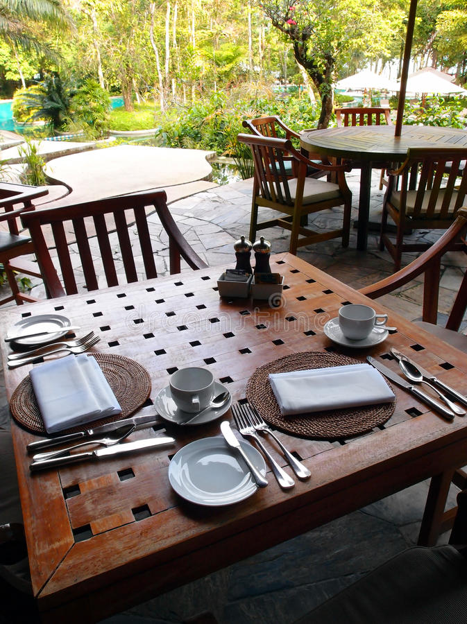 Outdoor dining restaurant, table cutlery settings. Outdoors eating in style, elegant place setting - A photograph showing an upscale patio restaurant in an eco stock photos