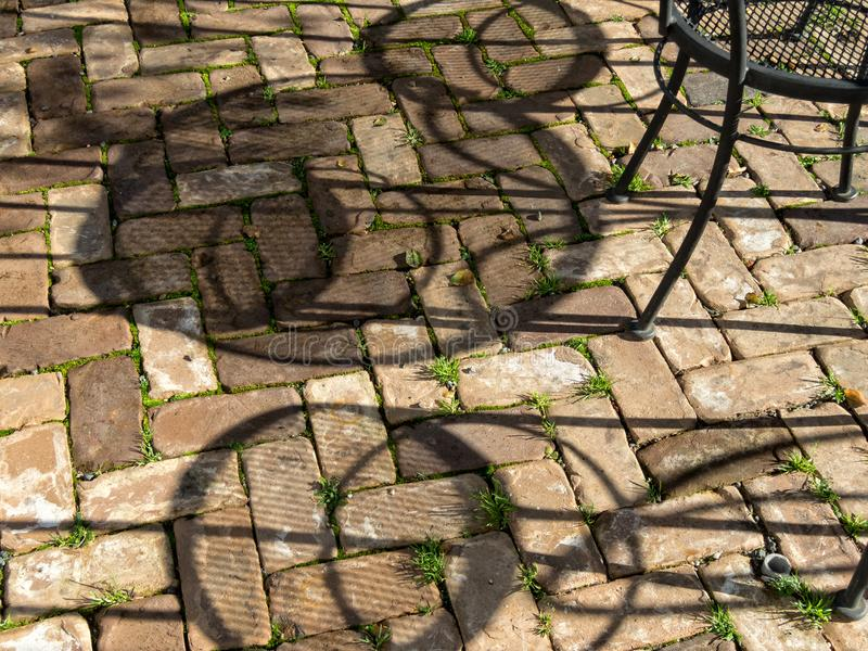 Outdoor dining, shadows on the pavers royalty free stock photo
