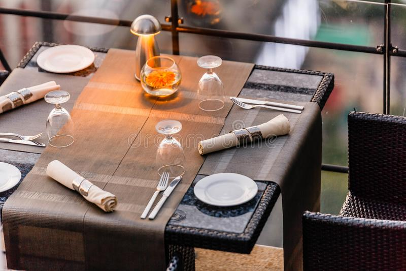 Outdoor dinning table set including plate, cutlery, napkin and wine glass.  stock image