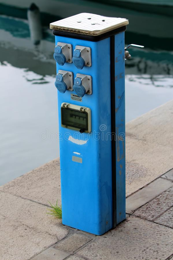 Outdoor electrical outlets with safety switches mounted on blue metal pole used for powering small boats in local harbor stock photo