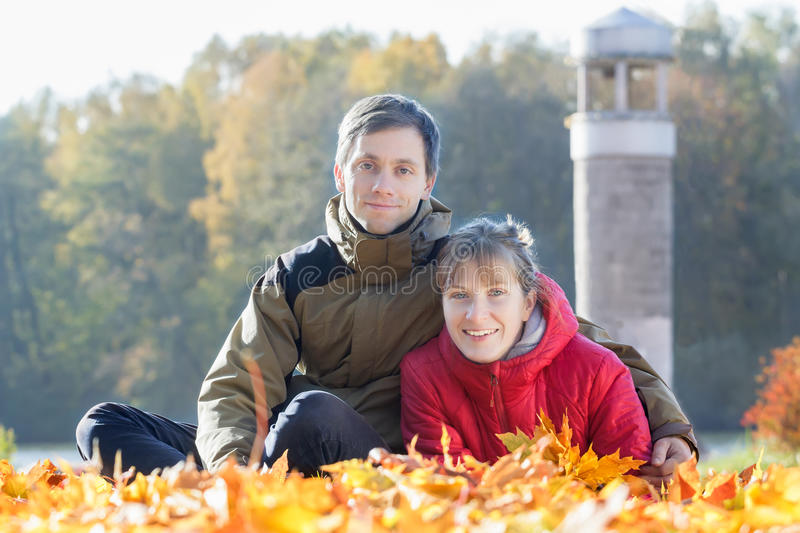 Outdoor family portrait of two young adult people in autumn park background. Outdoor family portrait of two young adult people in autumn leaves park background stock photography