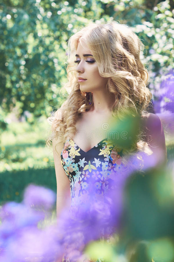 Outdoor fashion beautiful young woman surrounded by lilac flowers summer. Spring blossom lilac bush. Portrait of a girl blond stock photo