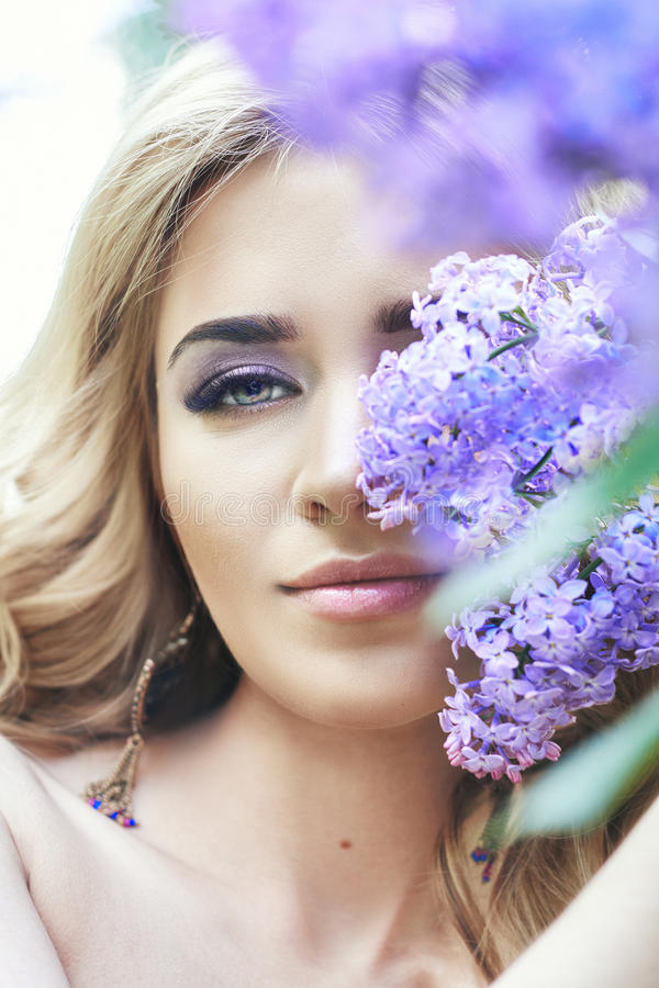 Outdoor fashion beautiful young woman surrounded by lilac flowers summer. Spring blossom lilac bush. Portrait of a girl blond royalty free stock image