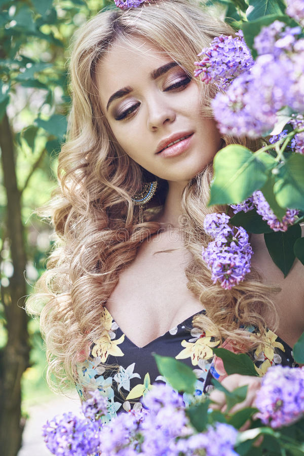 Outdoor fashion beautiful young woman surrounded by lilac flowers summer. Spring blossom lilac bush. Portrait of a girl blond royalty free stock images