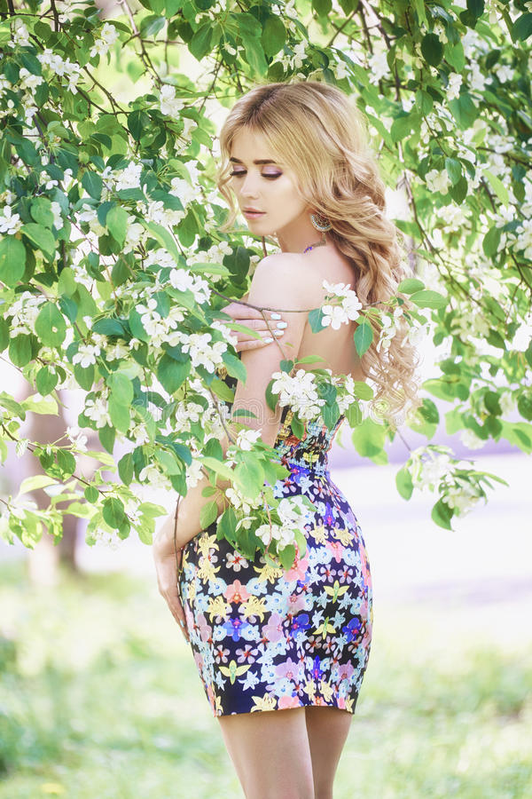 Outdoor fashion beautiful young woman surrounded by lilac flowers summer. Spring blossom lilac bush. Portrait of a girl blond stock image