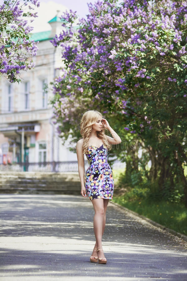 Outdoor fashion beautiful young woman surrounded by lilac flowers summer. Spring blossom lilac bush. Portrait of a girl blond royalty free stock photos
