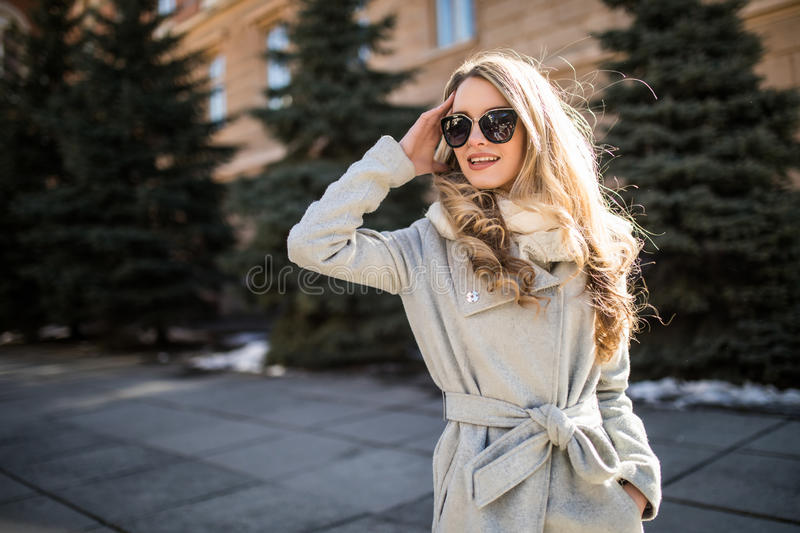 Outdoor fashion closeup portrait of young pretty woman in sunglases walking on street royalty free stock images