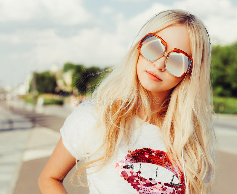 Outdoor fashion closeup portrait of young pretty woman in vintage sunglasses. Summer sunny day on street royalty free stock images