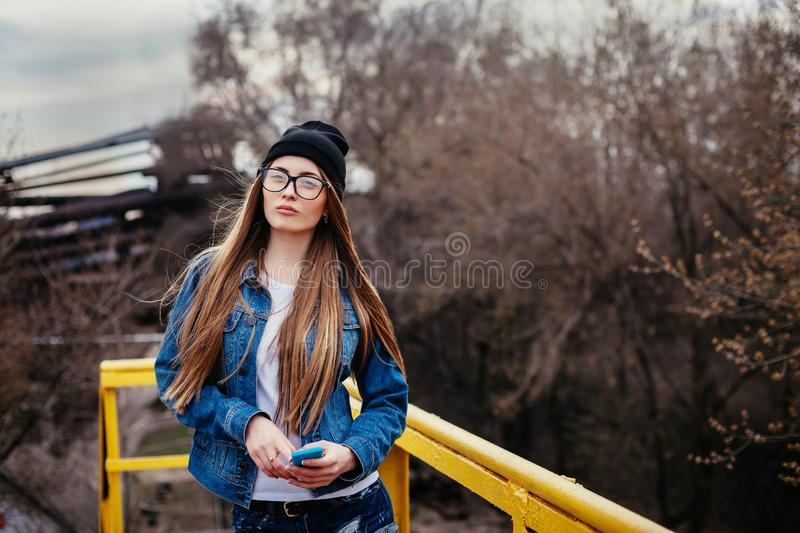 Outdoor fashion lifestyle portrait of pretty young girl, wearing in hipster swag grunge style urban background stock photography