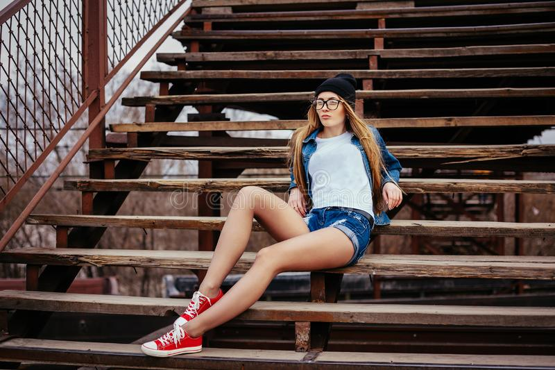 Outdoor fashion lifestyle portrait of pretty young girl, wearing in hipster swag grunge style urban background royalty free stock photography