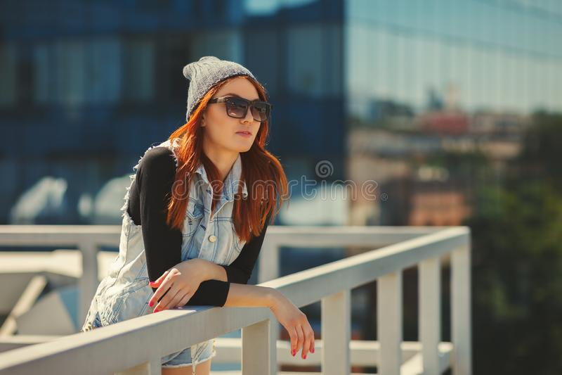 Outdoor fashion lifestyle portrait of pretty young girl, wearing in hipster swag grunge style urban background. Tomboy city royalty free stock photos