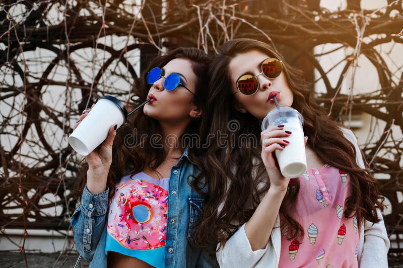 Outdoor fashion lifestyle portrait of two young beautiful women, dressed in denim outfit, mirrored sunglasses, enjoy a. Stroll, drink coffee, bright stylish royalty free stock photos