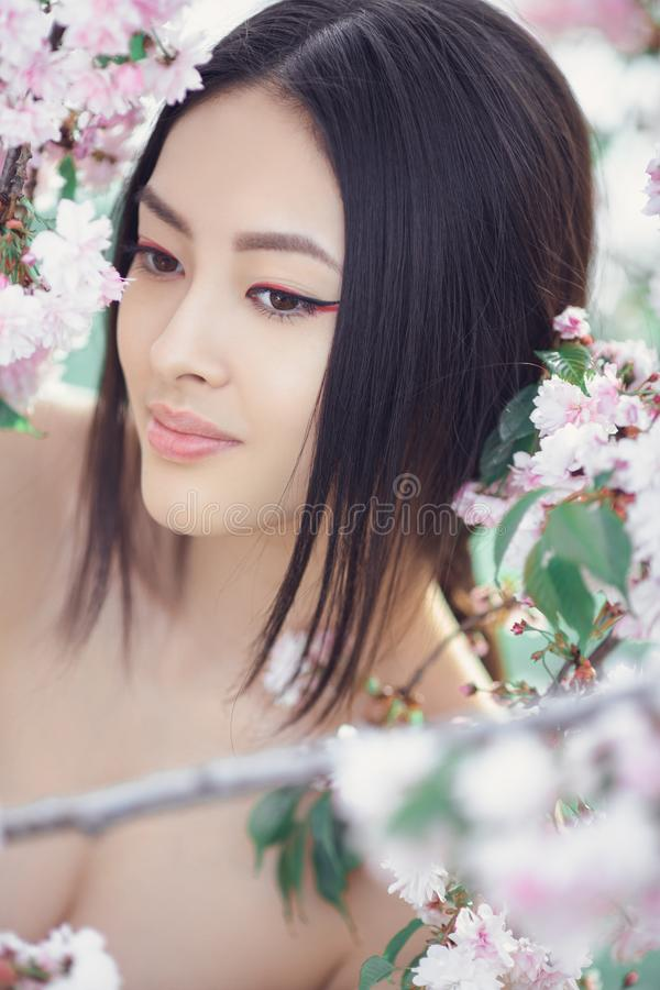 Portrait of a beautiful fantasy asian girl outdoors against natural spring flower background. Outdoor fashion photo of beautiful young asian woman surrounded by royalty free stock image