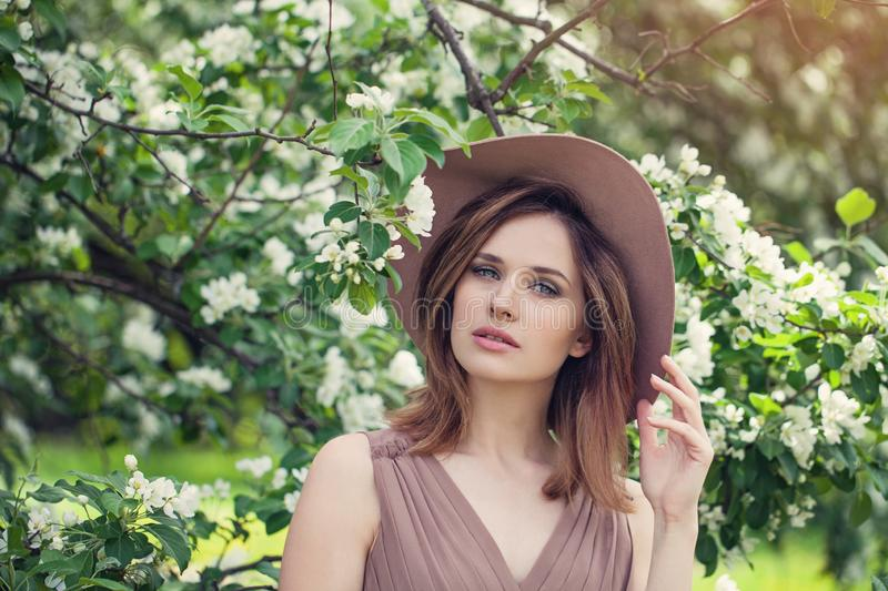 Outdoor fashion photo of beautiful young woman in flowers. Spring blossom stock photo