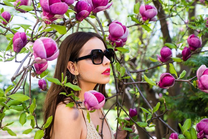 Outdoor fashion photo of beautiful young woman surrounded by flowers. Portrait of a young woman in sunglasses. Beautiful royalty free stock photos