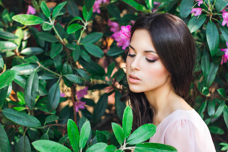 Outdoor fashion photo of beautiful young woman surrounded by flowers. Spring blossom. Portrait of young beautiful woman posing among spring blossom trees stock photos
