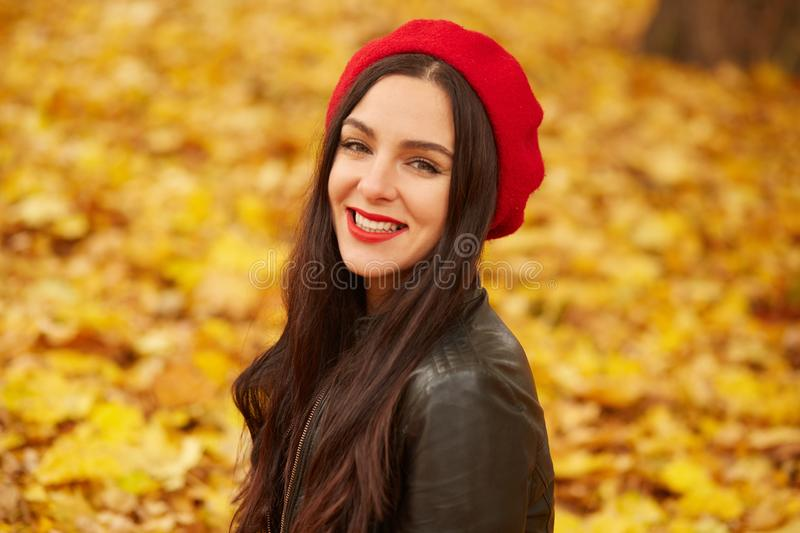 Outdoor fashion photo of young beautiful lady surrounded autumn leaves, woman in autumn park, happy attractive dark haired woman royalty free stock images