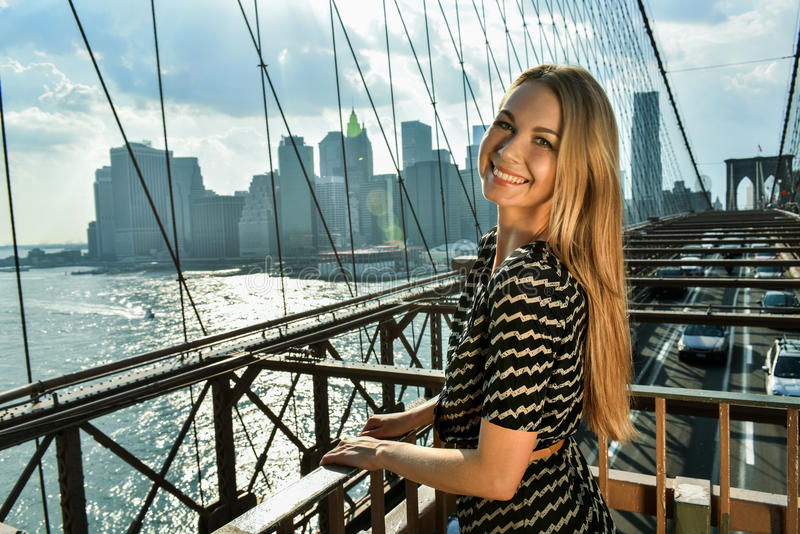 Outdoor fashion portrait of beautiful smiling young woman posing on the Brooklyn Bridge. stock photo