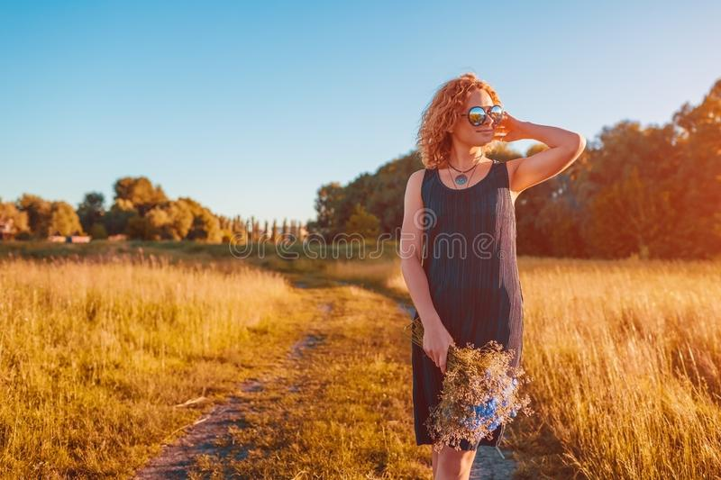 Outdoor fashion portrait of beautiful young woman with red curly hair holding flowers. Summer clothing and accessories. royalty free stock photos