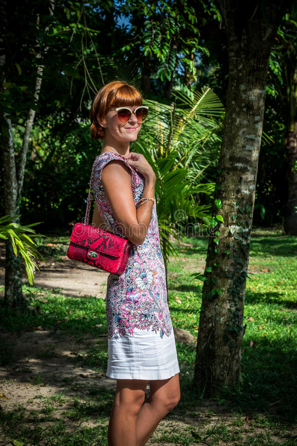 Outdoor fashion portrait of glamour sensual young stylish lady in sunglasses with luxury handmade snakeskin python bag royalty free stock image
