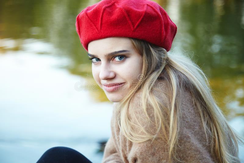Fashion portrait of pretty smiling blonde girl wearing red beret stock photo