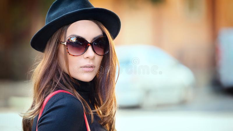 Outdoor fashion portrait of smiling young woman wearing trendy black hat and big retro sunglasses stock images