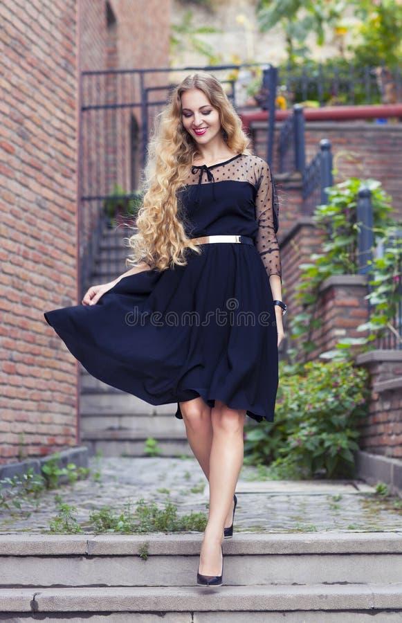 Outdoor fashion portrait of stylish lady wearing trendy black dr. Outdoor fashion portrait of glamour sensual young stylish lady wearing trendy black dress royalty free stock images