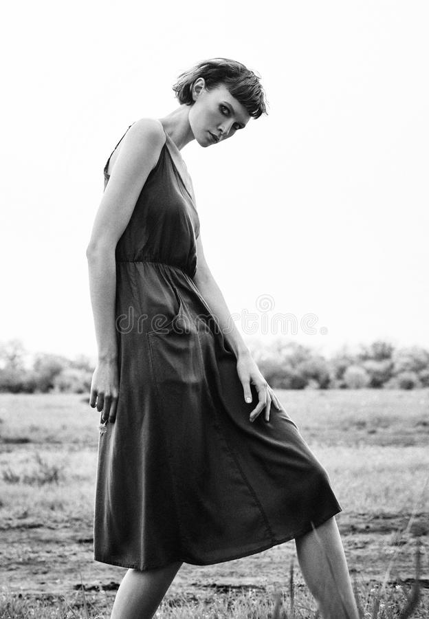 Outdoor fashion shot: beautiful girl in field. Portrait of lovely young woman in dress. Black and white. Film grain effect stock photo