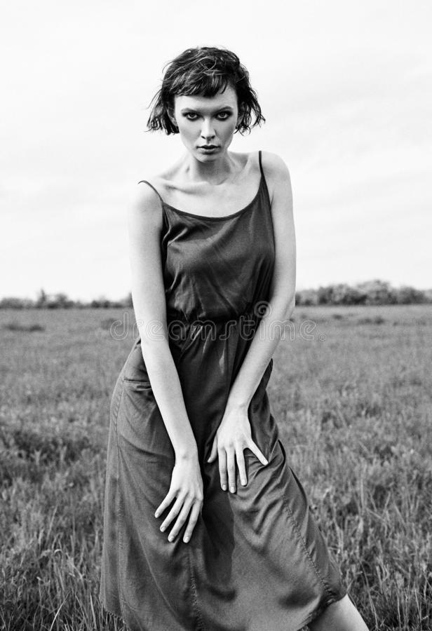Outdoor fashion shot: lovely sad girl in meadow. Portrait of beautiful young woman in dress. Black and white. Film grain effect royalty free stock photo