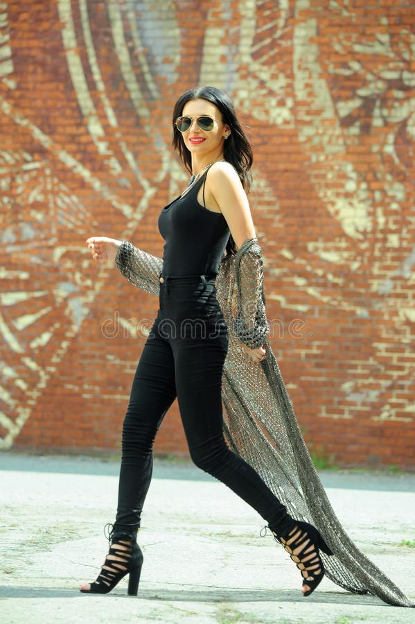 Outdoor fashion street style photo of pretty young woman in trendy outfit walking in the city. stock photo