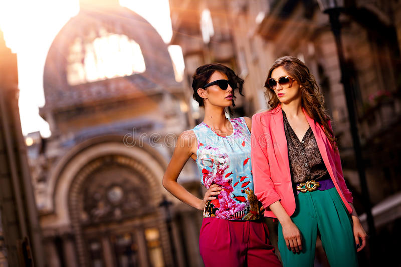 Outdoor fashion street young women. Fashion shot of two elegant beautiful girls in the sunset wearing sunglasses. Two young women outdoor on the street. Shopping stock photography
