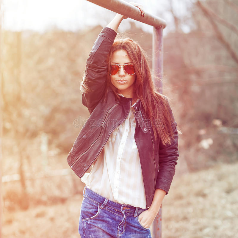 Outdoor fashion toned colors portrait of young woman in jea. Ns, jacket and sunglasses royalty free stock photography