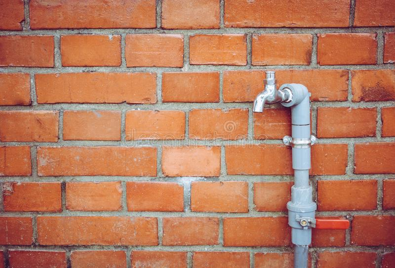 Outdoor faucet water tap with gray PVC pipe and red valve on red brick wall background texture, water saving concept stock image