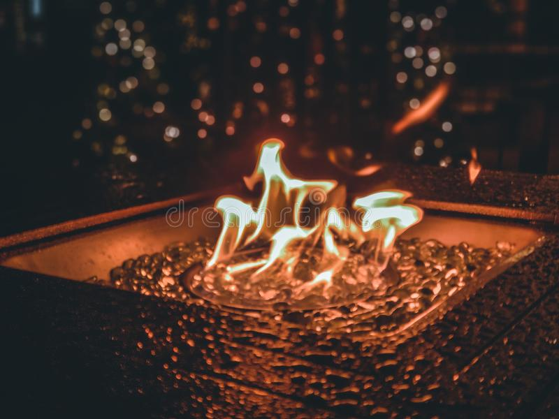 Flames dance over glass marbles in a fire pit. stock images