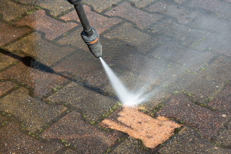 Outdoor floor garden cleaning with high pressure water jet. An Outdoor floor garden cleaning with high pressure water jet royalty free stock image
