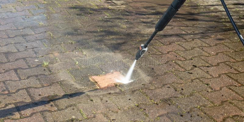 Outdoor floor Worker cleaning driveway  with a pressure water jet. An Outdoor floor Worker cleaning driveway  with a pressure water jet stock photos