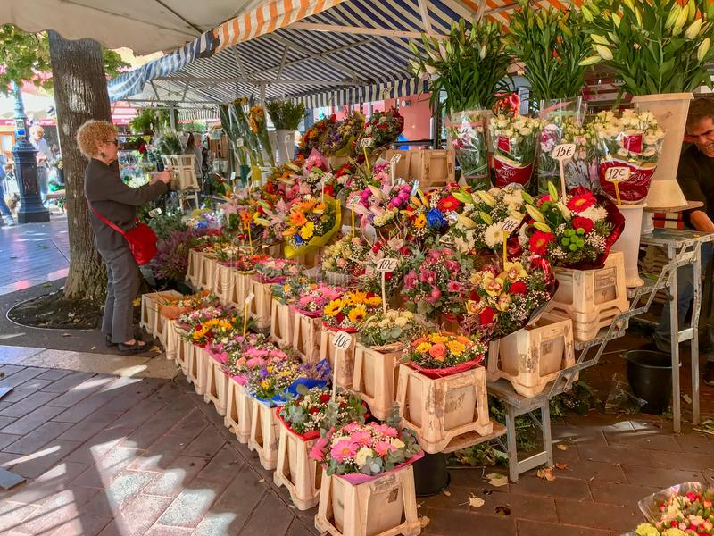 Outdoor flower market in Nice, France. Oct 2017: Woman looks at blooms in an outdoor flower market in Nice, France royalty free stock image