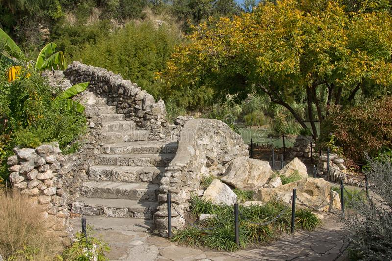 Stone pathway to a stone staircase in the park. Outdoor garden with blooming trees and lush green plants, stacked stone staircase and stone walkway royalty free stock photography