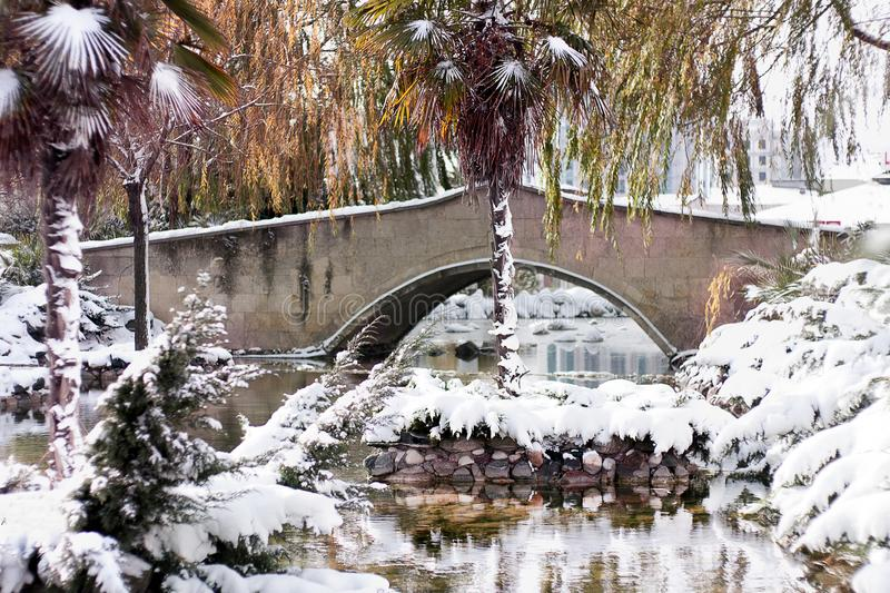 Outdoor garden and bridge with a dusting of snow. Winter Background. Snow royalty free stock image