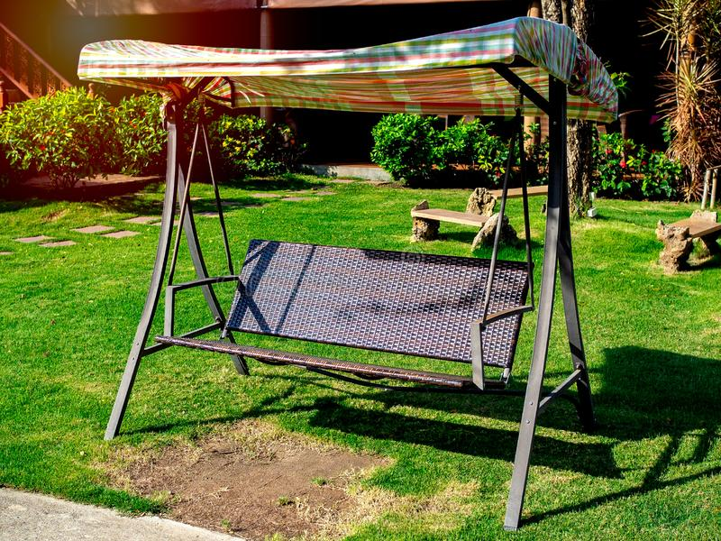 Outdoor garden rattan swing seat bench. On green grass in the garden on sunny day royalty free stock photography