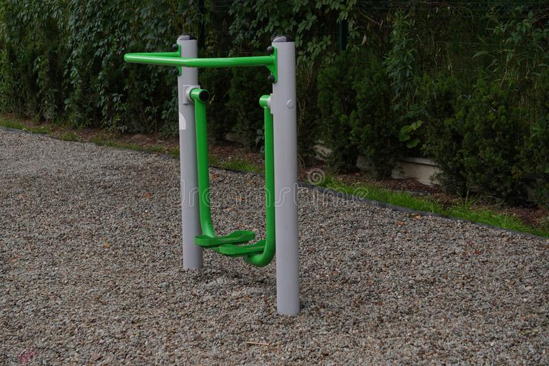 Outdoor green-gray iron exercise machine for sports. public gym, muscle building, exercise. The outdoor green-gray iron exercise machine for sports. public gym royalty free stock photography