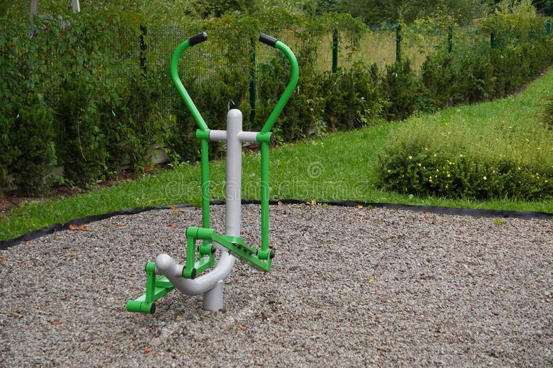 Outdoor green-gray iron exercise machine for sports. public gym, muscle building, exercise. The outdoor green-gray iron exercise machine for sports. public gym stock photo