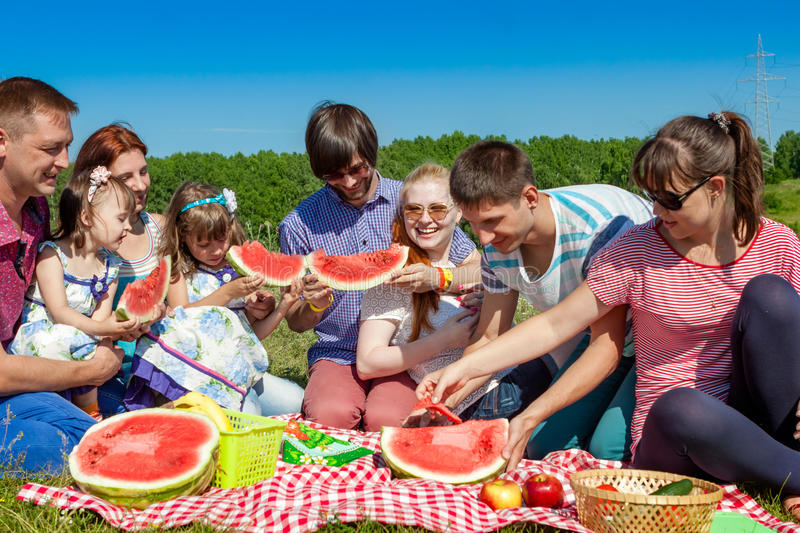 Outdoor group portrait of happy company having picnic on green grass in park and enjoying watermelon stock photo