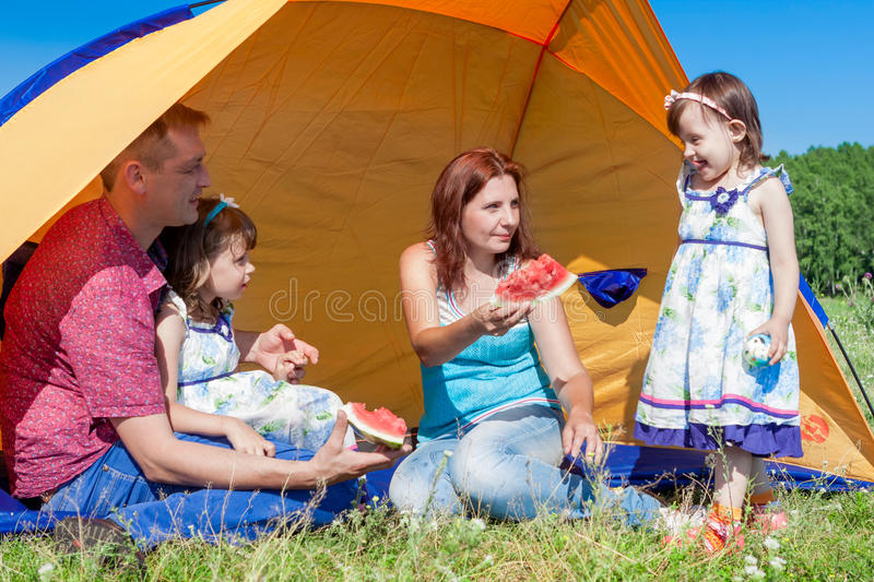 Outdoor group portrait of happy company having picnic near the tent in park and enjoying watermelon stock image