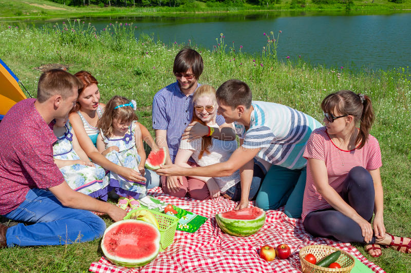 Outdoor group portrait of happy family having picnic near the lake and enjoying watermelon royalty free stock photography
