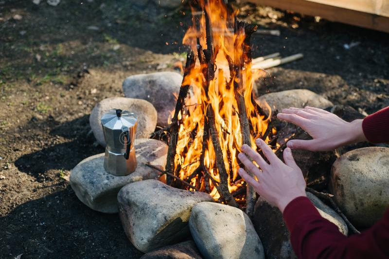 Outdoor horizontal image of traveler warming his hands by the campfire an in summer time. Rear view of traveler man in red jacket, sitting near to bonfire stock photography