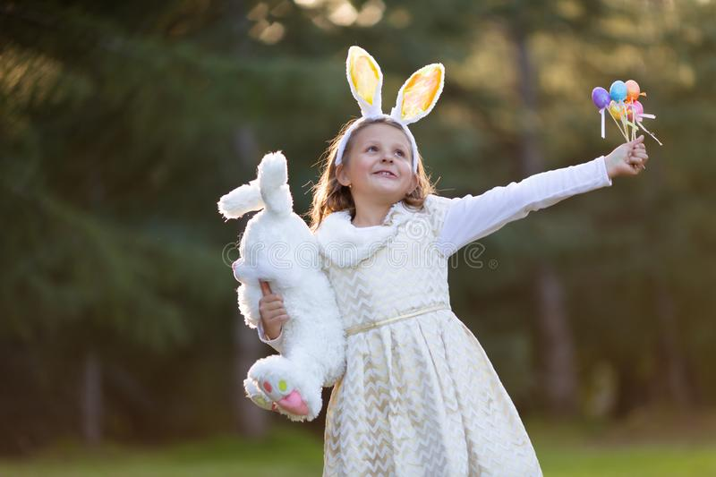 Outdoor horizontal portrait of little Caucasian girl in festive dress with big white plush bunny toy and Easter eggs royalty free stock photo