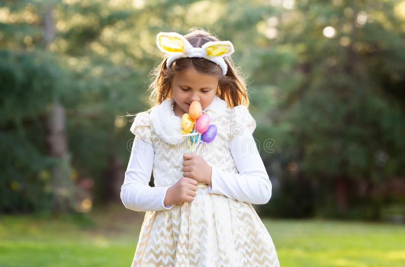 Outdoor horizontal portrait of little Caucasian girl in festive dress with Easter eggs decoration royalty free stock images