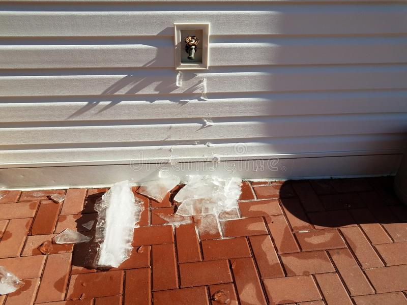 Outdoor hose spigot with ice and red bricks in winter royalty free stock image